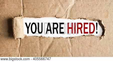 You Are Hired.text On White Paper On Torn Paper Background