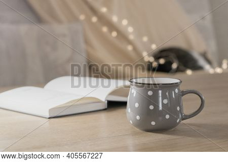 Cup Of Hot Tea And Book On The Table, Cozy Home Interior With Sleeping Cat On The Background