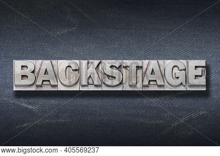 Backstage Word Made From Metallic Letterpress On Dark Jeans Background
