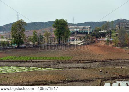 North Korea, Pyongyang Outskirt - April 30, 2019: Сountryside Landscape. Village And Agriculture Fie