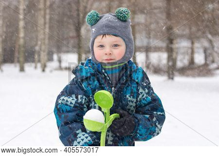 A Boy In A Winter Overalls Stands On The Street, In The Hands Of A Snowball. The Child Makes Snowbal