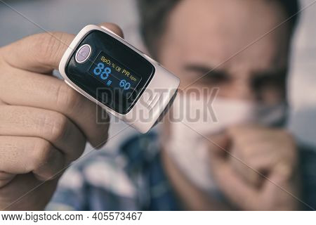 Pulse Oximeter On A Mans Finger. Oxygen Saturation Of The Blood. A Patient In A Medical Mask Measure