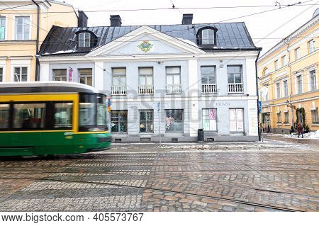Finland, Helsinki. January 26, 2021 Green Tram In Front Of A Gray Building. The First Stone House In