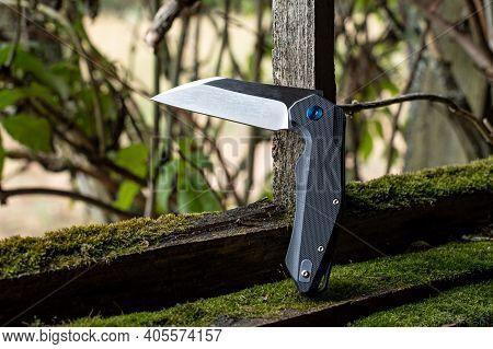 A Sharp Knife In A Bent Position. Knife On The Background Of A Bush. Daylight