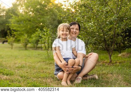 Mother And Daughter Having Fun In The Park. Happy Family Concept. Beauty Nature Scene With Family Ou
