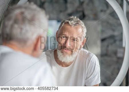 Grey-haired Man Looking At His Reflection In The Mirror