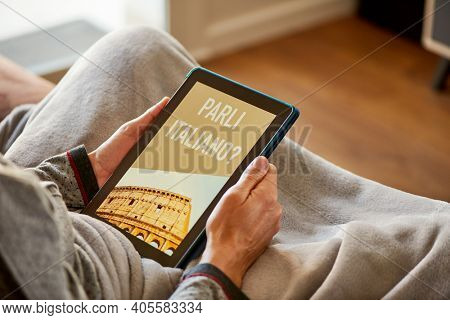 closeup of a young caucasian man, sitting comfortably in a sofa wrapped in a warming gray blanket, having his tablet in his hands with the text do you speak italian in its screen