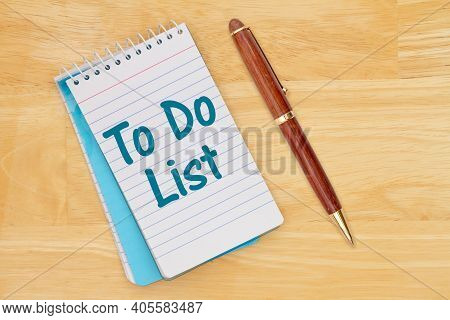 To Do List On A Retro Lined Paper Notepad On A Wood Desk With A Pen