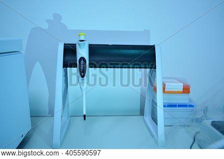 Pipette Dispenser For Laboratory Diagnostics. Single-channel Pipette Dispenser On A Black Matte Base