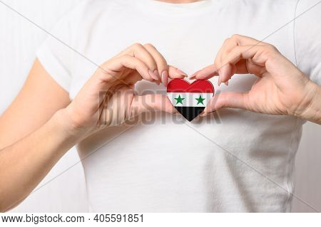 Love Syria. The Girl Holds A Heart In The Form Of The Flag Of Syria On Her Chest. Syrian Concept Of