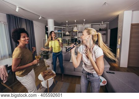 Group Of Young Women Spend Free Time In Karaoke, Sing And Have Fun Together, With Friends, At Home.