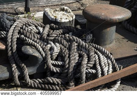 Old Worn And Frayed Rope On Dock Side