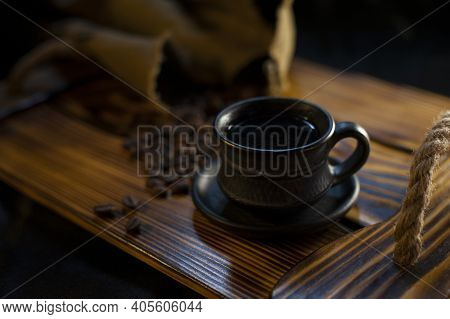 Black Cup With Coffee And Coffee Beans On A Wooden Surface. Fully Roasted Coffee Beans On A Rough Ru