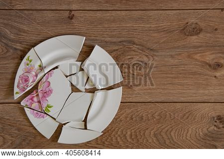 Shards Of A Broken Plate On The Wooden Floor. Broken White Ceramic Plate On The Wooden Floor. Broken