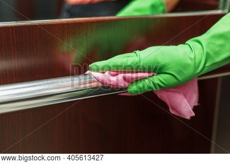 Antiviral Disinfection With An Aerosol Sanitizer For Elevator Handrails, With Female Hands In Gloves