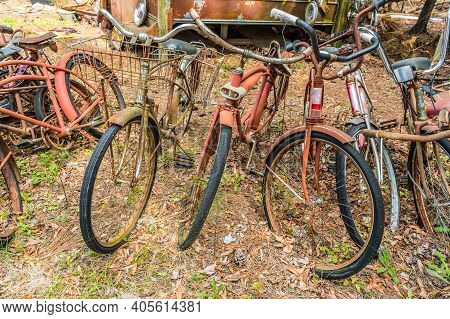 A Group Of Old Vintage Bicycles Left Outdoors To Rot And Decay With Other Junk Debris In The Woods