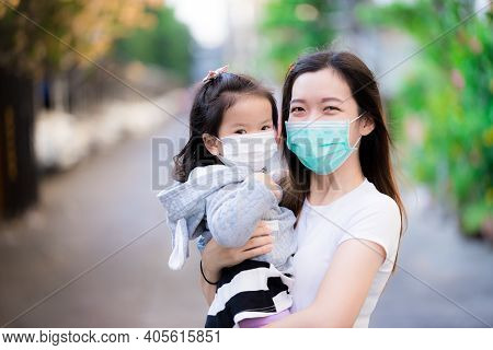 Asian Family And Adorable Child Girl Wearing Medical Face Masks On Public Roads. Mother And Kid Wear
