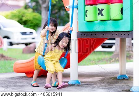 Asian Older Sister Taught The Little Sister To Play Swings. Sisters Are Playing Blue Swing On Playgr