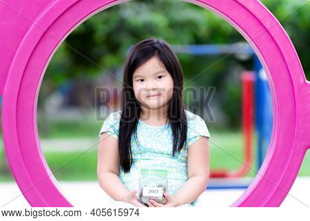 Portrait Of Happy Child Asian Girl Wearing Blue Skirt, Carrying Silver Bowl With Small Paper Written
