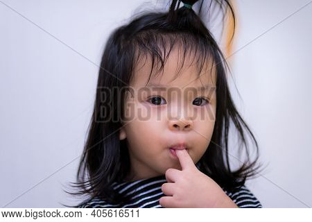 Closeup Adorable Asian Kid Girl Is Sucking A Finger Which Can Cause Germs Into The Body And Cause Il