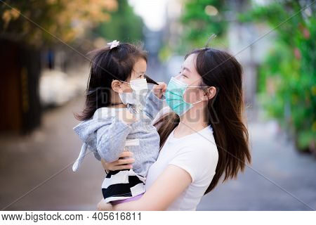 Mother Holds Her Daughter. Mother And Child Wear A Mask. Both Looked At Each Other Warmly. The Conce