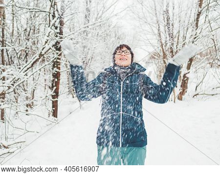 Smiling Woman Is Playing With Snow. Fun In Snowy Winter Forest. Woman Laughs As She Walks Through Wo
