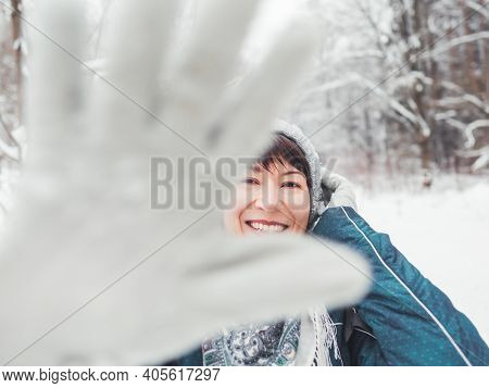 Smiling Woman Is Closing Camera With Hand In Warm Glove. Fun In Snowy Winter Forest. Woman Laughs As