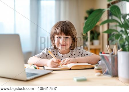 Distance Learning Online Education. Caucasian Smile Kid Boy Studying At Home With Laptop, Writing In
