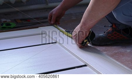 Taking Measurements On A Light Wooden Canvas Lying On The Floor When Installing Metal Fasteners Usin