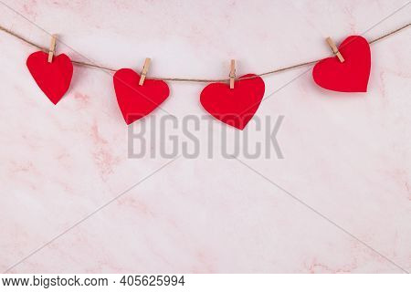 Red Heart Shaped Garland On Over Pink Wall Background. Valentine's Day Garland.