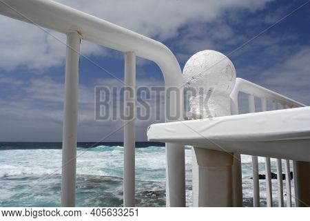 A View Of The Pristine Turqoise Ocean Through White Railings