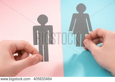 Hands Holding Paper Dolls Of Man And Woman On Pink And Blue Background