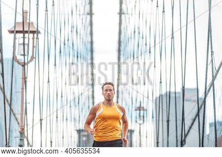 New York city runner training running on Brooklyn Bridge for Marathon race, fit athlete man on outdoor summer run jog.