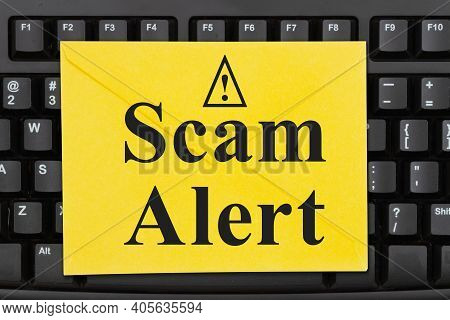 Scam Alert Message On A Yellow Envelope On A Black Keyboard