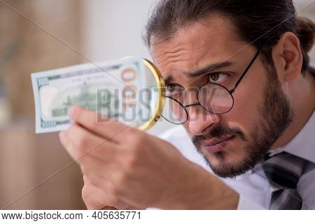 Young male bookkeeper in counterfeit bills concept