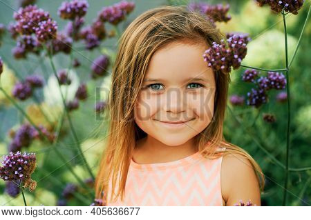 Outdoor Summer Portrait Of Adorable Little Girl Of 3 Or 4 Years Old, Posing In Purple Flowers