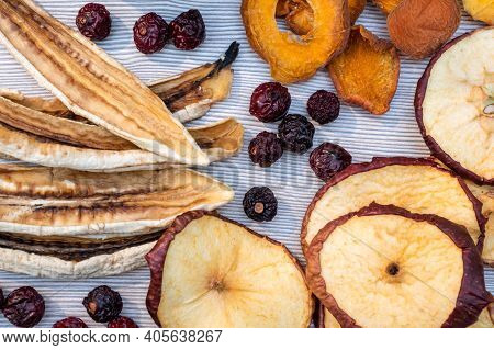 Sliced Dried Dehydrated Fruits And Berries On A Light Table. The Concept Of Home Preparation Of Drie