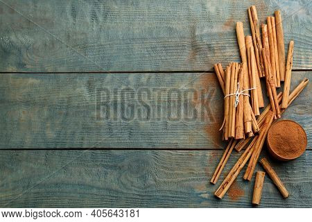 Aromatic Cinnamon Sticks And Powder On Light Blue Wooden Table, Flat Lay. Space For Text