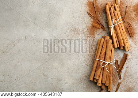 Aromatic Cinnamon Sticks And Powder On Grey Table, Flat Lay. Space For Text