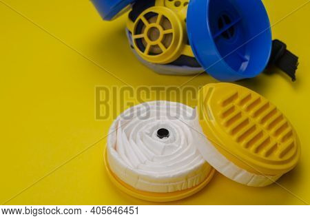 New Replacement Filters And Industrial Respirator On Yellow Background. Personal Respiratory Protect