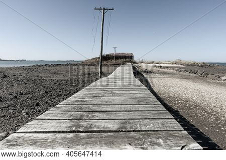 Rustic Wooden Walkway Leading To Old Waterside Shed And Power Pole With Cut Lines Dangling Of Ocean