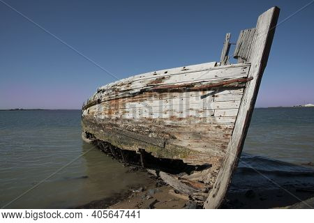 Rotting Holed Hulk Of Old Wooden Fishing Boat Beached On Shore Of Ocean Beach Road Southland New Zea