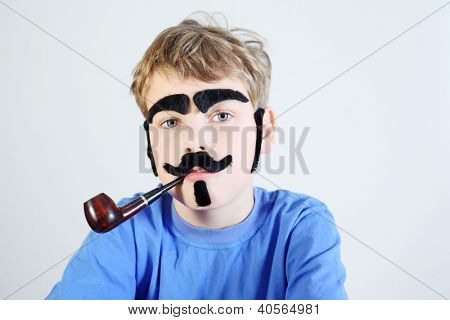 Little boy in blue with pipeful, fake mustache, eyebrows, beard and sideburns looks at camera.