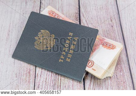 Labor Book And Russian Money On The Table. Payments Under An Employment Contract. Russian Translatio