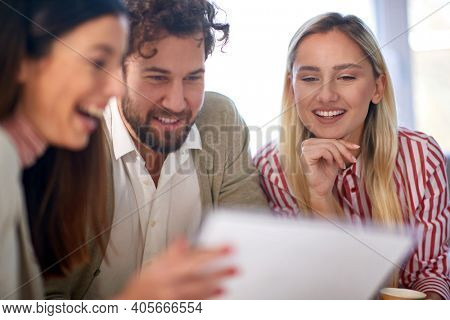 A group of young business people reading documents at a meeting in a relaxed atmosphere. People, business, meeting