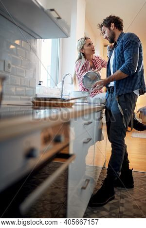 A young man helping girlfriend about housework in a relaxed atmosphere in the kitchen. Kitchen, housework, home, relationship