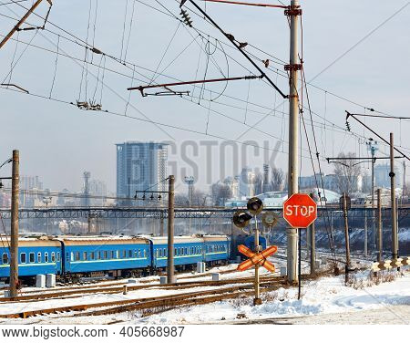 A Red Stop Sign At A Railroad Crossing Against The Backdrop Of Railroad Tracks, Blue Train Carriages