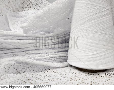 White Cotton Yarn In Bobbins And Fabric Made From This Yarn.