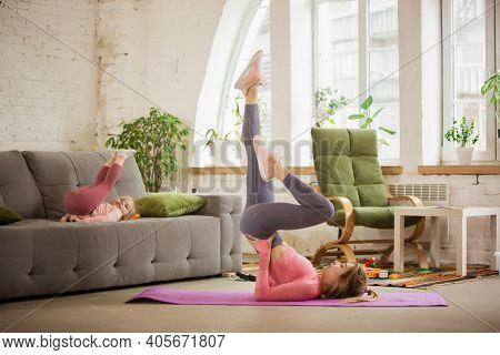 Balance Together With Daughter. Young Woman Exercising Fitness, Aerobic, Yoga At Home, Sporty Lifest