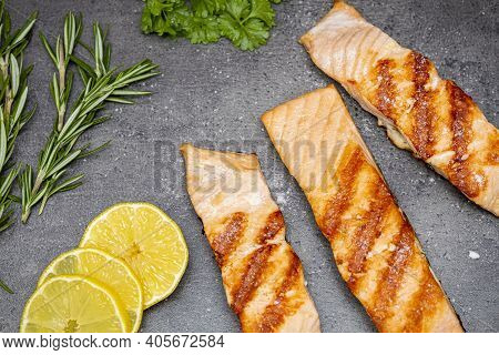 Grilled Salmon Fish, Three Pieces Of Salmon, Lemon, Rosemary And Parsley On A Dark Background. Top V